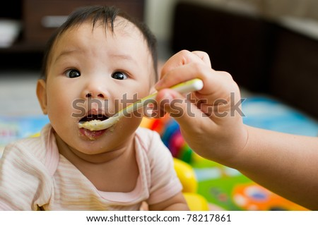 Six month old South East Asian Chinese baby girl being spoon fed - stock photo