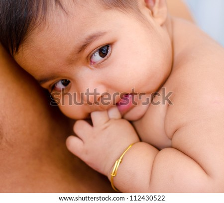 Six months old Indian baby girl is lying on daddy chest - stock photo