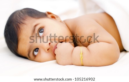 Six months old Indian baby girl sucking her fingers - stock photo