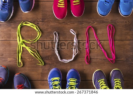 Six pairs of running shoes and shoelaces run sign on a wooden floor background - stock photo