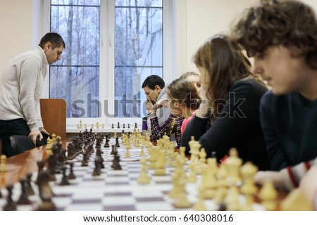 Six people (adults and children) play chess on table in chess club