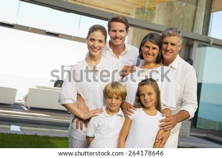 Six person family portrait in the backyard of a luxury house, jumping. - stock photo