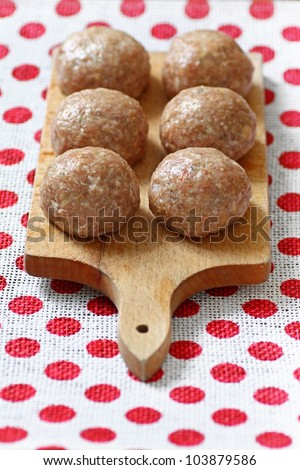 Six pork balls from minced meat laid on wooden cutting board - stock photo