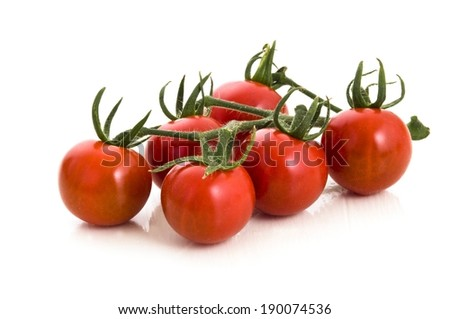Six ripe tomatoes still attached to the vine. - stock photo