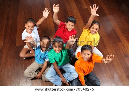 Six school children sitting in classroom hands up