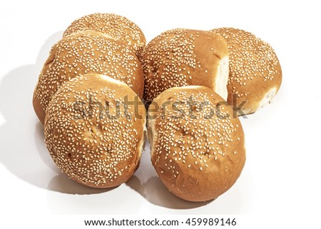 Six stacked freshly baked  golden hamburger rolls sprinkled with sesame seeds on white background