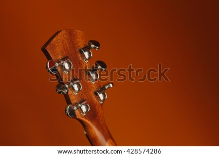 six-string acoustic guitar on a red background.