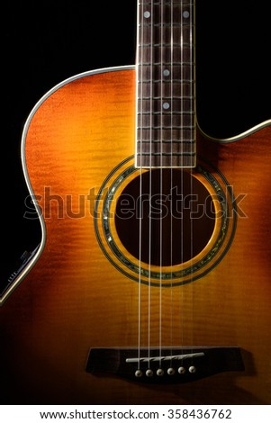 Six string acoustic guitar with a black background. - stock photo