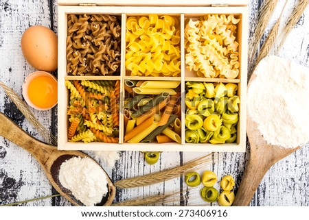 six types of pasta, tortellini and other products on textured wooden table - stock photo