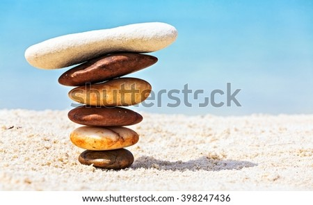 Six white and brown stones are on  sandy beach - stock photo