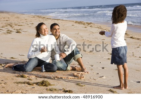 Six year old African-American girl gathering shells with parents on beach - stock photo
