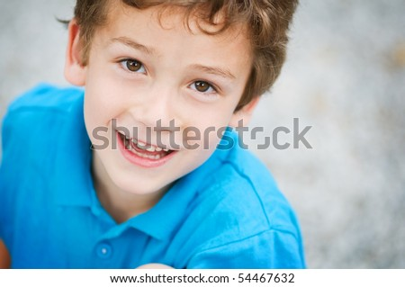 six year old boy looking up with a big smile - stock photo