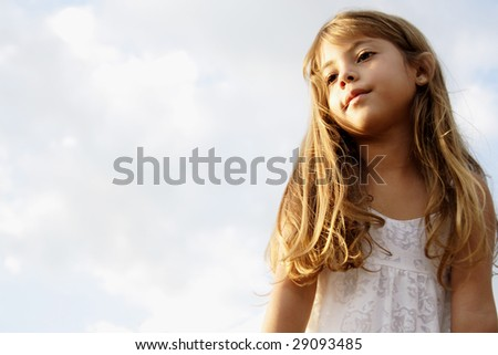 Six year old girl dreaming in an outdoor park. - stock photo