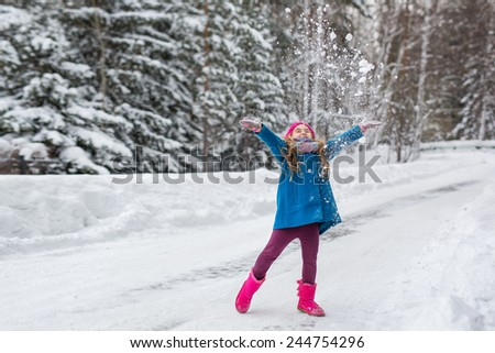 Six year old girl dressed in a blue coat and a pink hat and boots throws snow up - stock photo