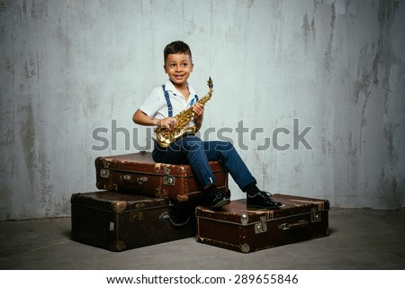 six years old boy sit with saxophone on old suitcases. instagram toned - stock photo