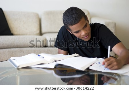 Sixteen year old boy working on his homework.