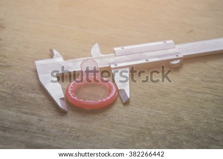 Size is important,condom and Vernier Caliper on wood background,valentine concept,selective focus,vintage tone - stock photo