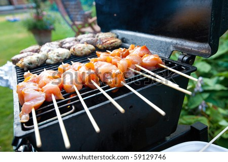 Sizzling burgers and chicken kebabs on hot barbecue outdoor.