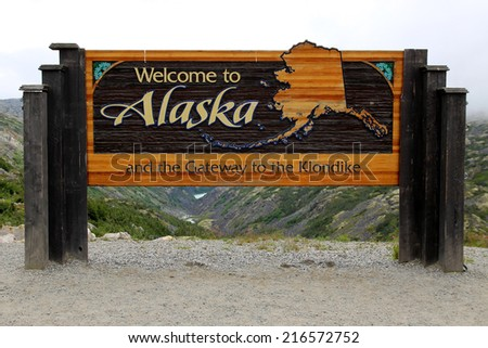 """SKAGWAY, ALASKA, UNITED STATES - AUGUST 6, 2014: The """"Welcome to Alaska and The Gateway to the Klondike sign"""" welcomes visitors to Alaska near Skagway. - stock photo"""