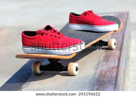 skateboard and sneakers at skatepark  - stock photo