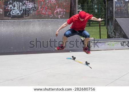 Skateboarder doing a jumping trick at skateboard park - stock photo