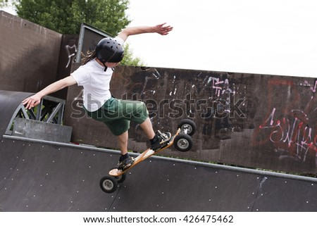 Skateboarder doing a jumping trick at skateboard park with mountainboard.  - stock photo