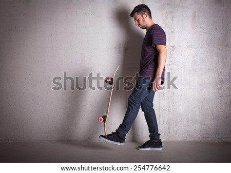 Skateboarder doing a skateboard trick, against concrete wall. - stock photo