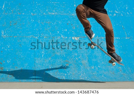 Skateboarder doing a skateboard trick - ollie - at skate park. - stock photo