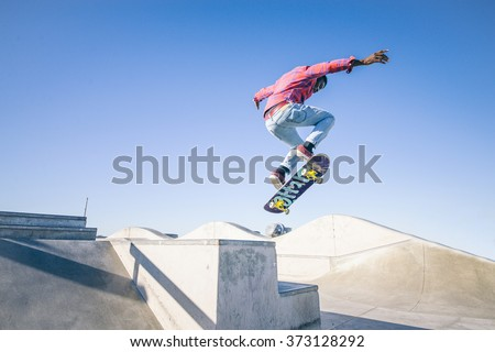 Skateboarder doing a trick in a skate park - stock photo