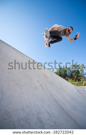 Skateboarder flying over a ramp on blue clear sky.