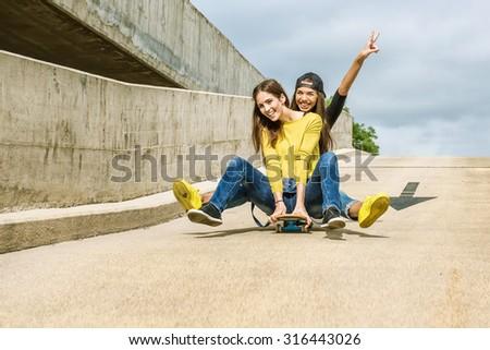 Skateboarder girlfriends roll down the slope - stock photo