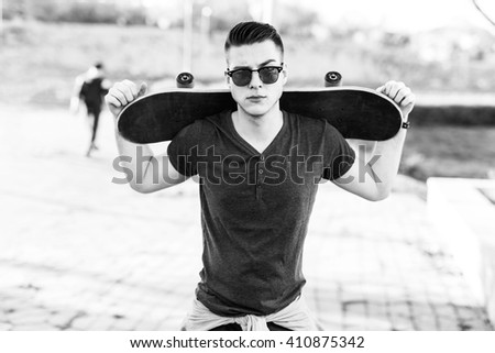 Skateboarder holding his skate in his arms behind his head. Depth of field, selective focus, black and white - stock photo