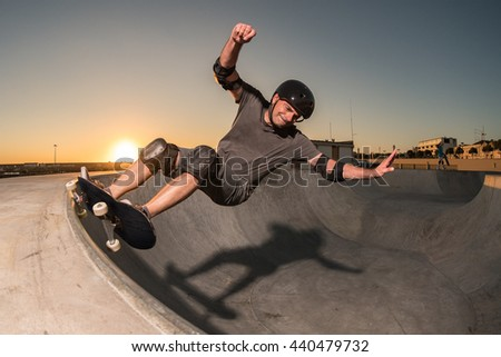 Skateboarder in a concrete pool at skatepark on a beatiful sunset. - stock photo