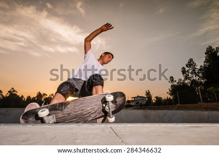 Skateboarder in a concrete pool at skatepark on a beautiful sunset.