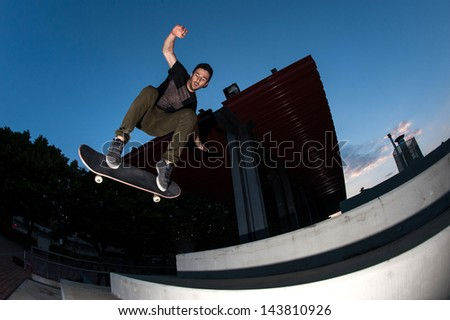 Skateboarder jump in the street from below, night time. - stock photo