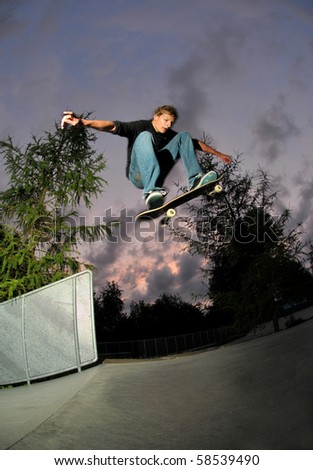 skateboarder jumping high at full speed at the skatepark after sunset(slightly motion blurred). - stock photo
