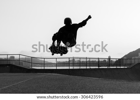 skateboarder jumping in a bowl of a skate park - stock photo