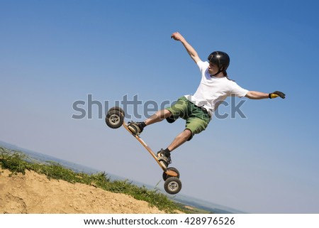 Skateboarder jumping with mountainboard over the hill . Bright blue sky in the background - stock photo