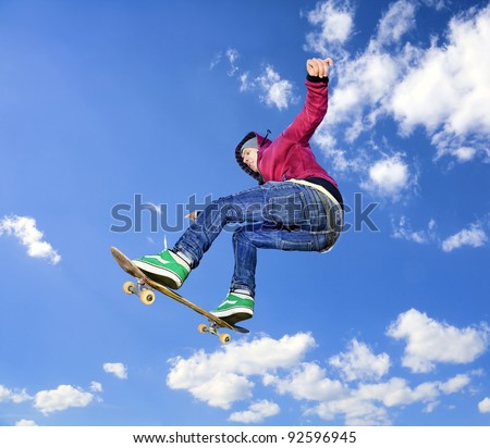 Skateboarder jumps high in air on background the blue sky with clouds - stock photo
