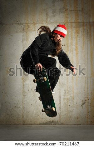 Skateboarder performing tricks with grungy wall as background - stock photo