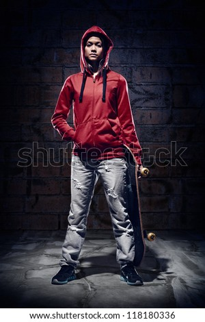 skateboarder portrait extreme sport skater with grunge wall and red hoodie - stock photo