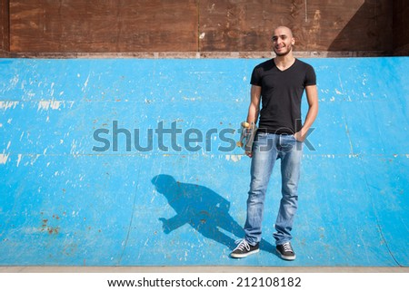 Skateboarder portrait standing on half pipe at skate park. - stock photo