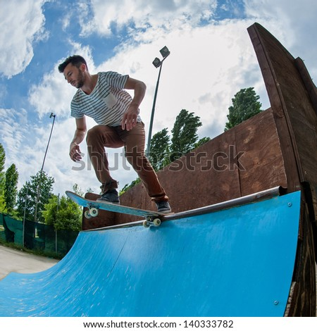 Skateboarder rolling down from halfpipe at skatepark. - stock photo