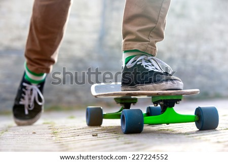 Skateboarder setting his board in motion by pushing off with one foot in an urban setting, representing the youth (sub) culture - stock photo