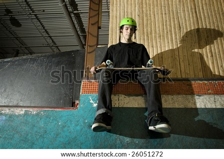 Skateboarder sitting on ramp holding his board - stock photo