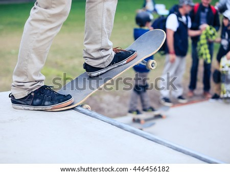 Skateboarder standing on a ramp in skate park ready to ride skate board and do tricks. Concrete outdoor park, focus on skateboard, feet and shoes - stock photo