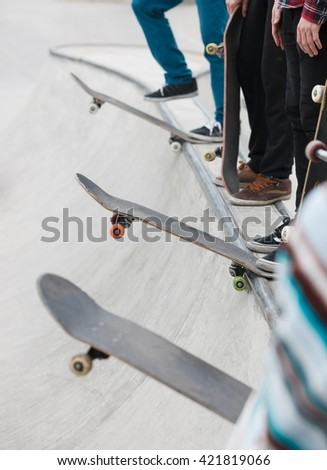 Skateboarders standing in a line on concrete ramp. Skateboarding contest or competition in outdoor skatepark. Dangerous extreme sport, popular among youth - stock photo