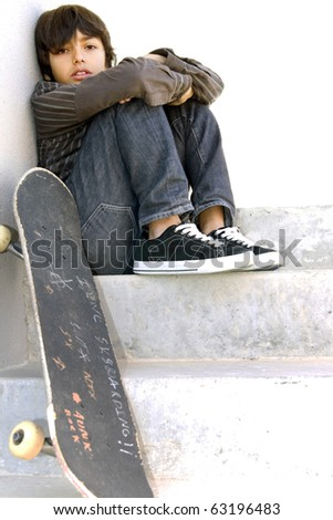 Skater boy: Boy looking bored is sitting on concrete steps with his skateboard. White copy-space - stock photo