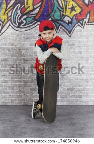 Skater boy with his skateboard in front of brick wall. He is looking at camera with a smile
