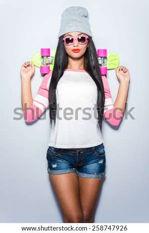 Skater girl. Beautiful young African woman in funky clothes holding colorful skateboard while standing against grey background  - stock photo